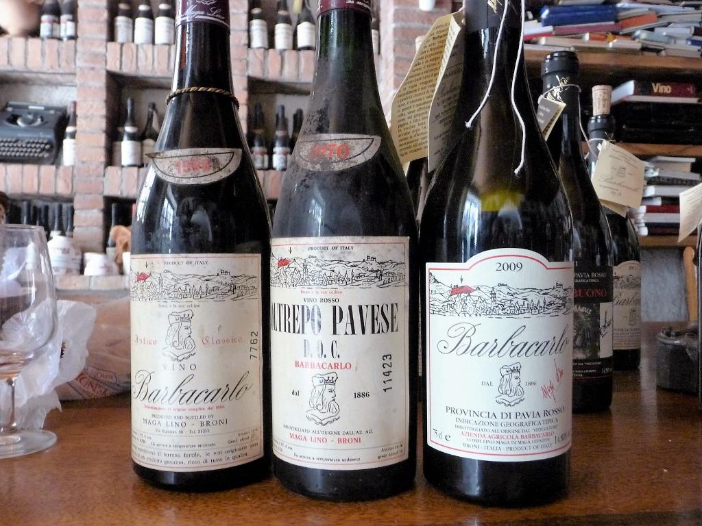 Die Etiketten des Weins Barbacarlo im Wandel der Jahre. Im Hintergrund sieht man eine Flasche mit dem angehängten Etikett, auf dem Lino jeden Jahrgang poetisch zusammenfasst. Foto: Gabriella Grassullo und Ezio Gallesi