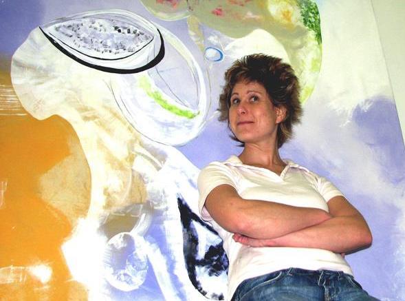 Man sieht Anja Pauseback in ihrem Atelier vor einem ihrer Bilder.