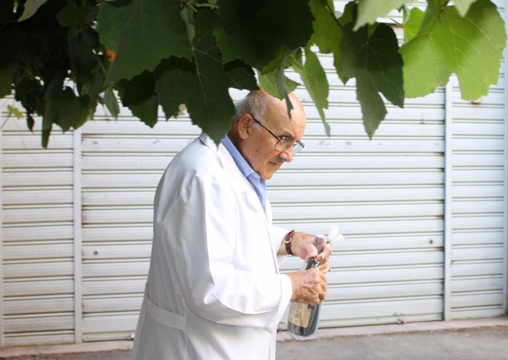 Si vede Professor Giovanni Russo nel suo cortile in un gabbiano bianco portando una bottiglia