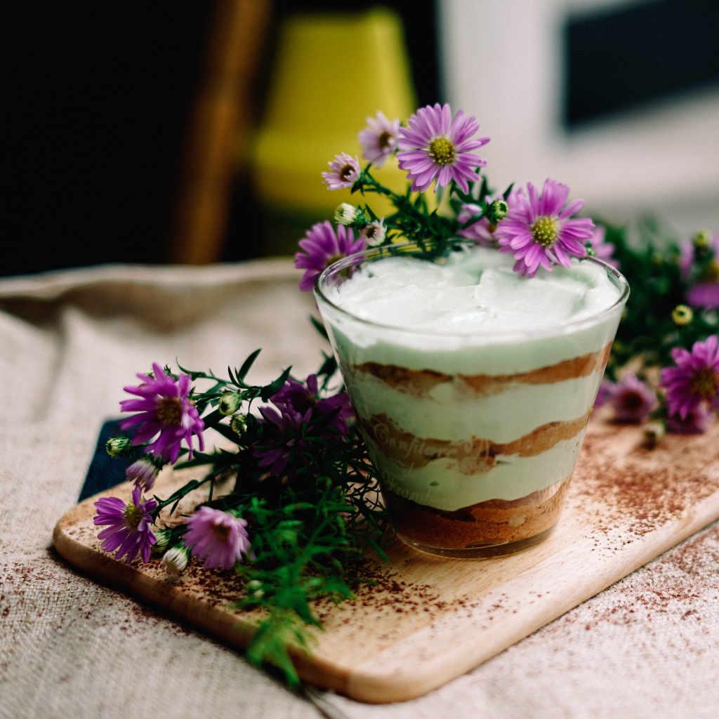 Im Glas geschichtes Tiramisu mit Blumen dekoriert. Illustration zum Artikel zum Ursprung und der Etymologie von Tiramisu von Katrin Walter – simply walter