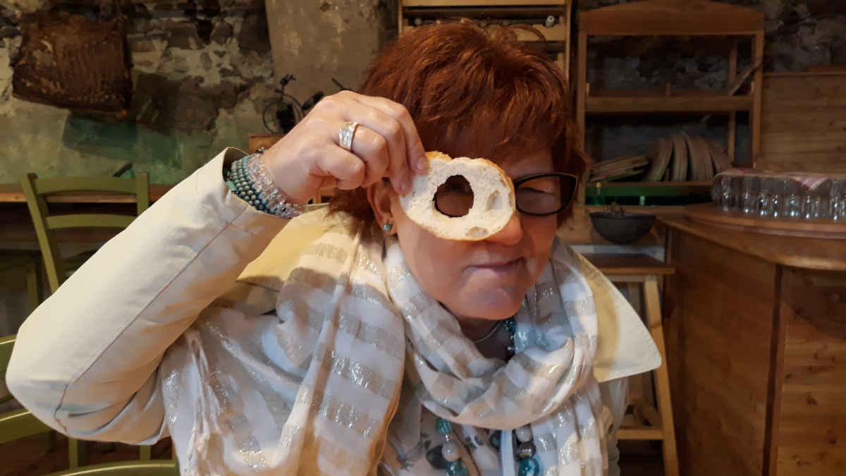 Katrin Walter hat den Durchblick … sie zeigt es, in dem sie durch ein Loch in der Brotscheibe schaut. Cembratal im Mai 2018.