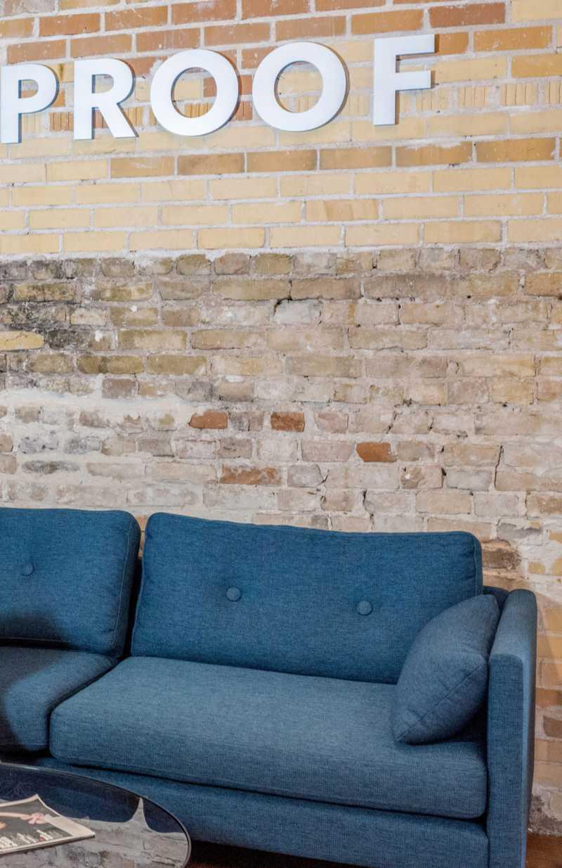 """Blaue Couch vor Ziegelwand mit dem Schriftzug """"Proof"""". Ab und an lohnt es sich, eigene Kommunikation auf den Prüfstand zu legen. Katrin Walter - simply walter"""