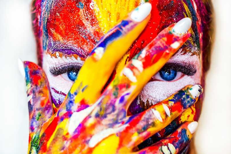 """""""Ist alles so schön bunt hier!"""" sang Nina Hagen in ihrem Song TV-Glotzer. Du siehst eine Frau voller bunter Farbe mit Hand vor dem Gesicht. Bild zum Text über Farbe im Design von Katrin Walter - simply walter"""