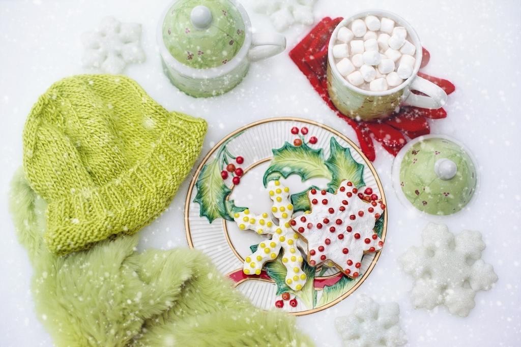 Winterzeit 2017. Hier dargestellt mit grüner Mütze, Schal, roten Handschuhen, sowie Weihnachtsgebäck und heißem Kakao im Schnee.